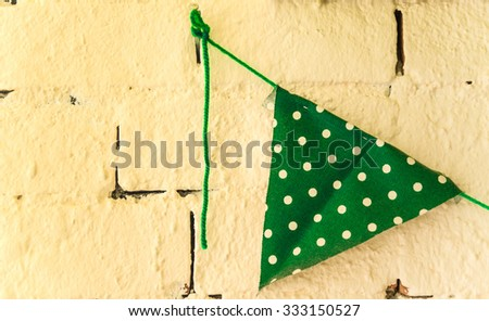 The wall cream color decorative with party flag of green and white polka dots, Selective focus. - stock photo