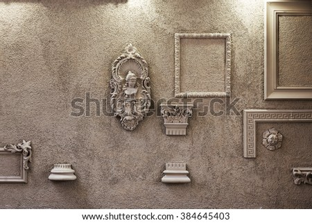 The wall is decorated with frescoes and an empty frame framed lighting. - stock photo