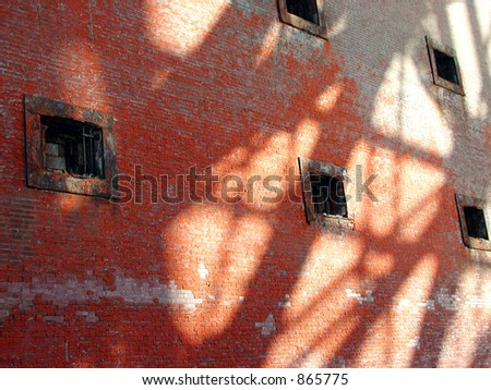 The wall of a historic brick fort with shadows cast by the Golden Gate bridge in San Francisco - stock photo
