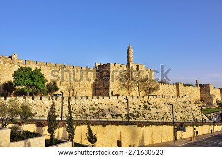 The walls of the eternal Jerusalem at sunset. Warm evening light illuminates the ancient walls and Tower of David - stock photo