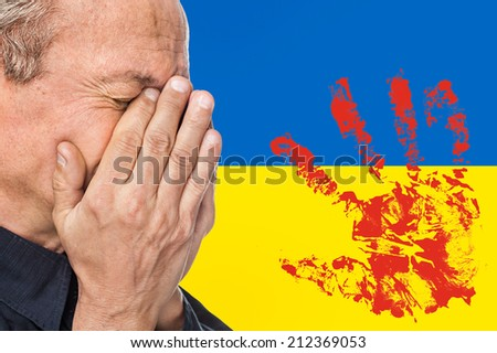 The war in Ukraine. Elderly man covered his face against of Ukrainian flag with bloody handprints - stock photo
