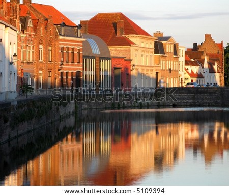the warm glow of Bruges buildings reflects into a nearby canal - stock photo