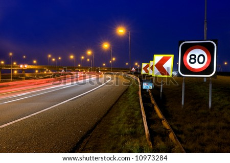 The warning signs on a motorway junction at night - stock photo