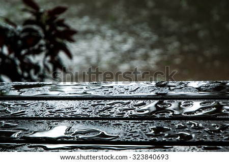 The water drops on wooden garden table, center focus for background.  - stock photo