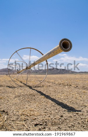 The water irrigation pipes in the dry Southern California farmland.  - stock photo