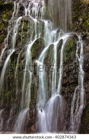 the waterfall among the rocks - stock photo