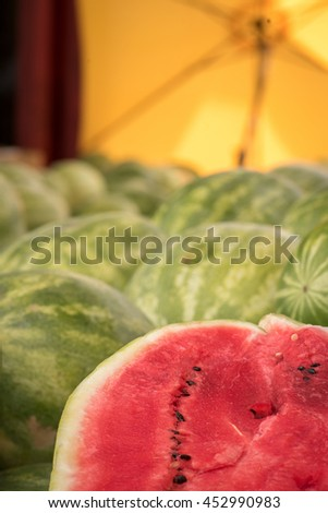 The watermelon is an summer fruit plant with long, weak, trailing or climbing stems which are five-angled and up to 3 m (10 ft) long. These watermelons are a favorite at the local Farmer's Market. - stock photo