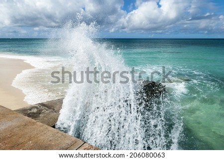 The wave suddenly splashes into the mall in Cockburn Town on Grand Turk island (Turks and Caicos). - stock photo