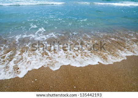 The wave surges on sandy coast - stock photo