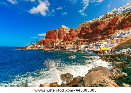 The waves beat against the rocks on a sunny summer day at Old port Ammoudi of Oia village at Santorini island in Aegean sea, Greece - stock photo