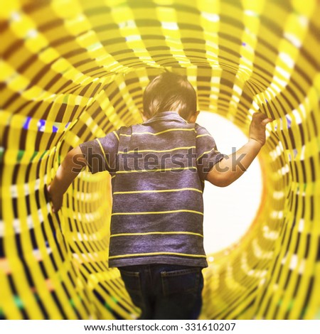 the way to the fabulous world. the concept of the transition bridge or tunnel between the different dimensions of space. a child comes in bright colorful tunnel, view from the back - stock photo