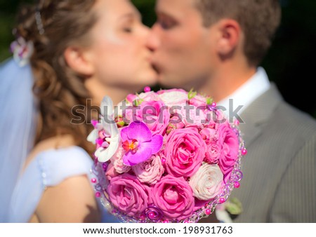 The Wedding Bouquet with Bride and Groom on the Background - stock photo