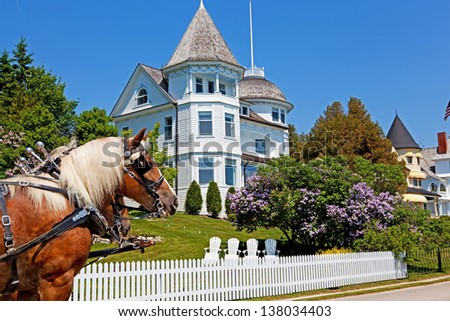 The Wedding Cake Cottage is shown on the West Bluff on Michigan's Mackinac Island. A horse stands in front and the lilacs out front are in full bloom - stock photo