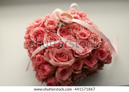 The wedding rings stand under bouquet - stock photo