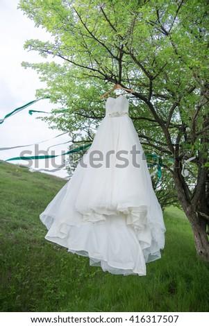 The wedding white dress hangs on a tree - stock photo