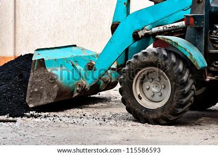 The wheel bulldozer works at asphalt laying. - stock photo