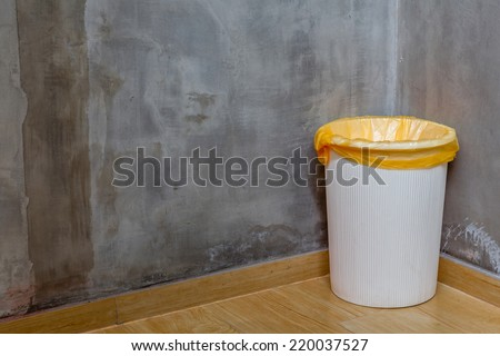 The white can bin at the corner on wooden floor with exposed cement background, for cleaning and recycle. - stock photo