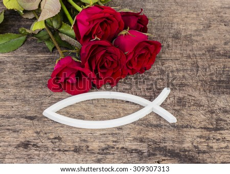 the white christian  and red roses  on wooden background - stock photo
