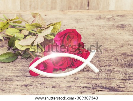 the white christian fish  with the light  effect and red roses  on wooden background - stock photo