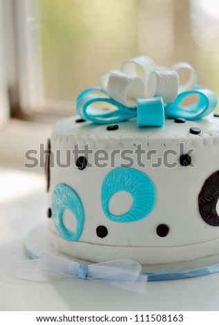 the white cream pie is decorated with a blue bow and drawing - stock photo