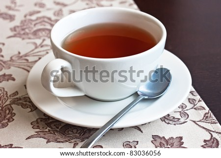 The white cup with black tea on dark wood - stock photo