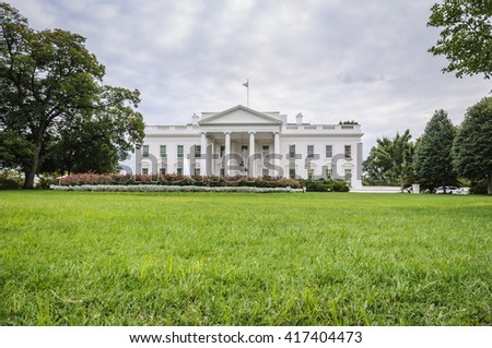 The White House in Washington D.C. at a cloudy day, green lawn in foreground, Executive Office of the President of the United States, USA - stock photo
