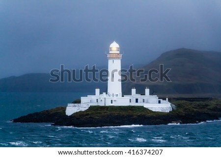 The white lighted lighthouse of Lismore at dusk with rough sea, near Mull and Oban, in the Inner Hebrides of Scotland. The guiding beacon gives reference, warning, safety to ships near the dim coast. - stock photo