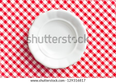 the white old plate on checkered napkin - stock photo
