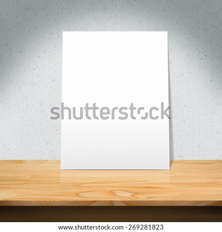 The white poster on a wooden table with Fabric texture background - stock photo