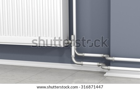 The white radiator and pipes of heating on the gray wall. - stock photo