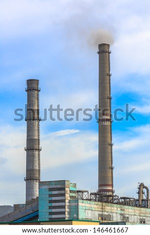 the white smoking from chimneys of a factory against a blue sky. - stock photo