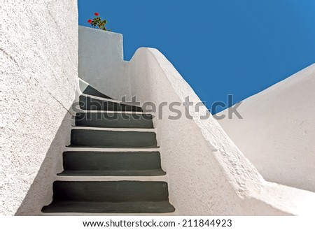 The whitewashed staircase decorated with geranium at Imerovigli, Santorini, Greece - stock photo