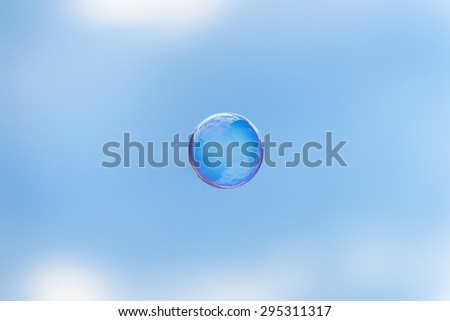The whole world in a soap bubble. Soap bubble flying in front of the blue sky and mirroring the clouds. - stock photo