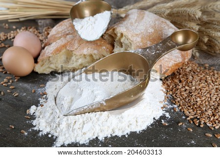 The wholemeal flour in scoops on wooden table on sackcloth background - stock photo