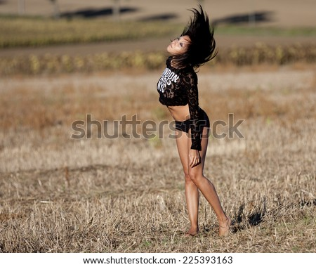 The wind blows in the black hair of a young woman. Closed eyes, she moves barefoot in a field of stubble. She wears a lacy black tshirt. - stock photo