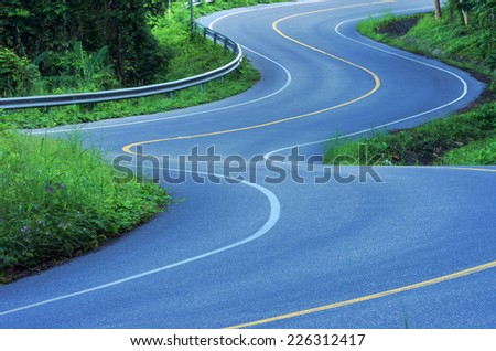 The winding road on the mountain in the country. - stock photo