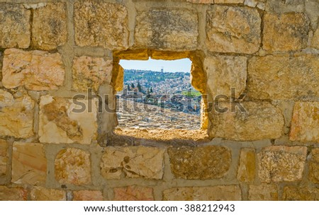 The window in old stone wall shows the old Jewish cemetery on the Mount of Olives, Jerusalem, Israel. - stock photo