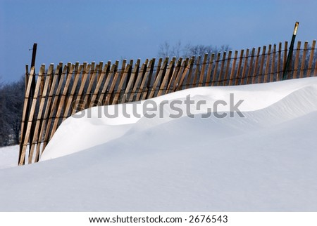 The winds and a snow fence have contrived to create a beautiful snow sculpture of drifts.  Full color. - stock photo