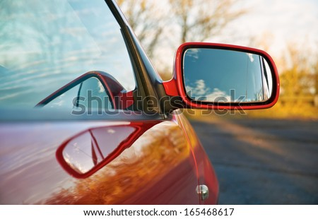 The wing mirror of a red car at sunset. - stock photo