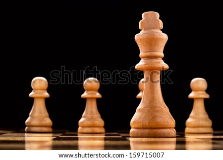 The winner - a light coloured wooden king chess piece - standing alone on a chessboard with the rest of the pieces visible in the distance behind it, selective focus - stock photo