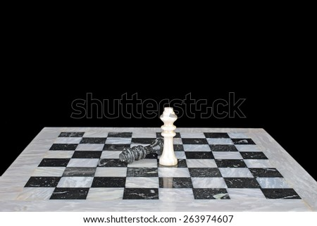 The winner. King beats the king, chess play on a marble chess board - stock photo