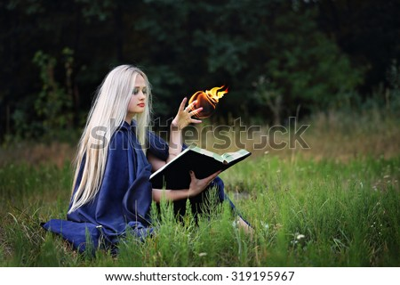 The witch with a book in the meadow practice witchcraft - stock photo