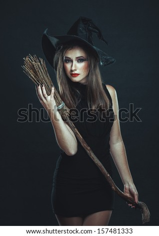 The   witch with a broom in a black dress in the studio - stock photo