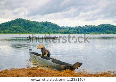 The woman and dugout boat on Lak lake, Central Highlands of Vietnam - stock photo