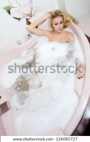 The woman blonde in bath  with foam - stock photo