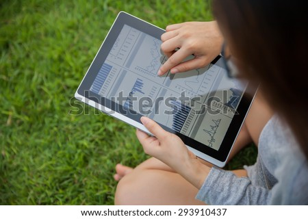 The woman checking reported profits in the garden. - stock photo