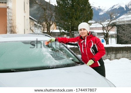 The woman clears car wind screen after cold night - stock photo