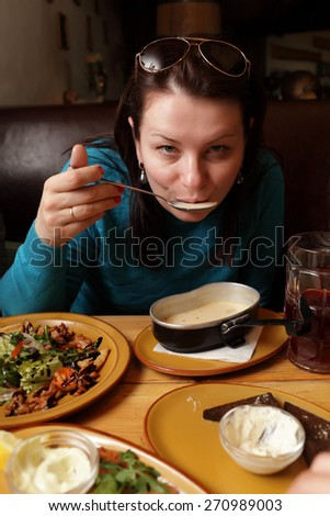 The woman eating soup in the restaurant - stock photo