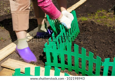 the woman establishes a green plastic fencing on a flower bed - stock photo