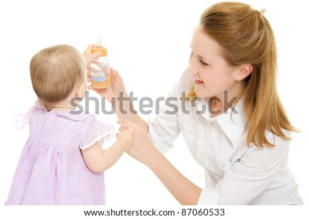 The woman gives the baby a bottle of infant formula. - stock photo